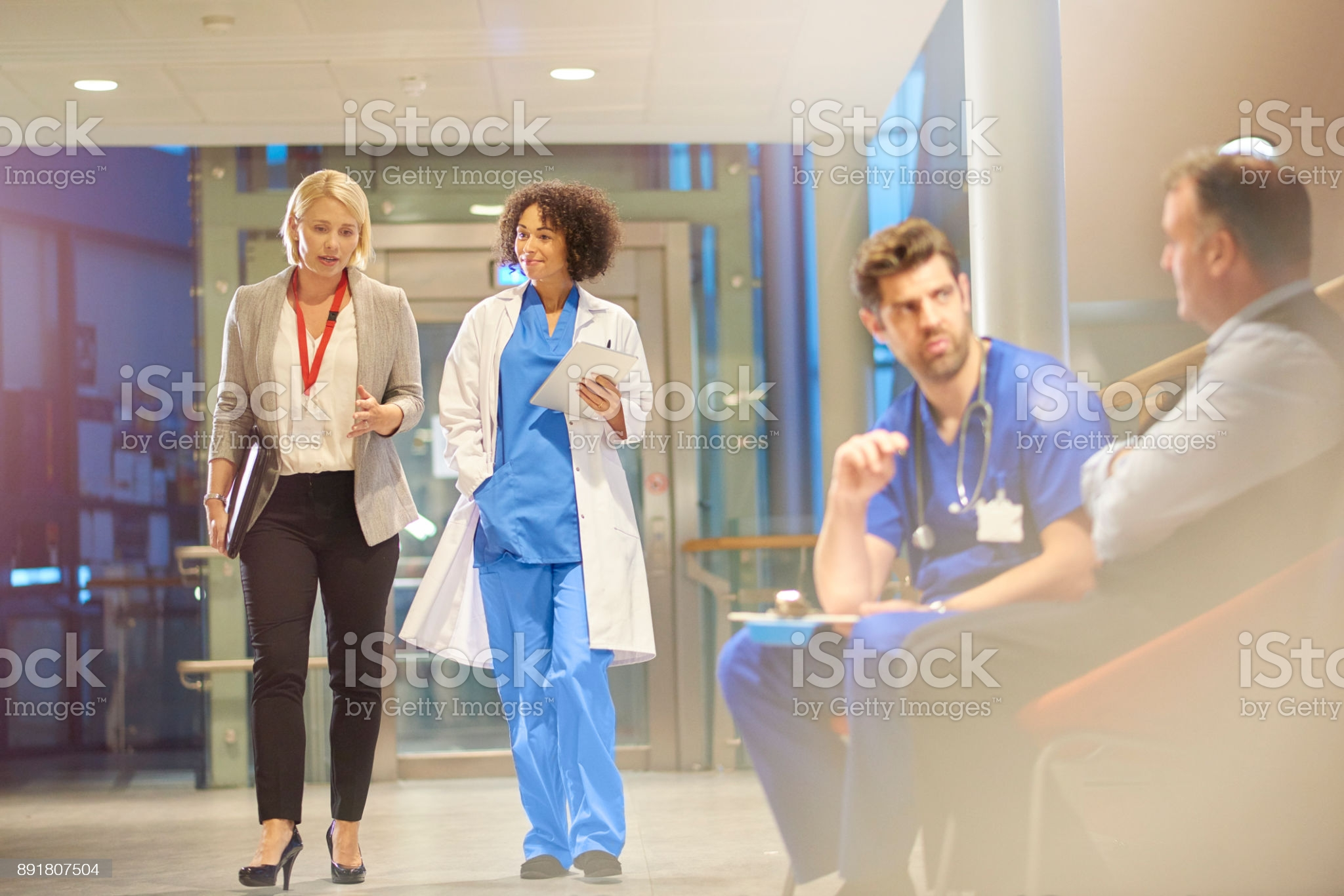 doctor-listening-to-sales-rep-in-hospital-corridor-picture-id891807504